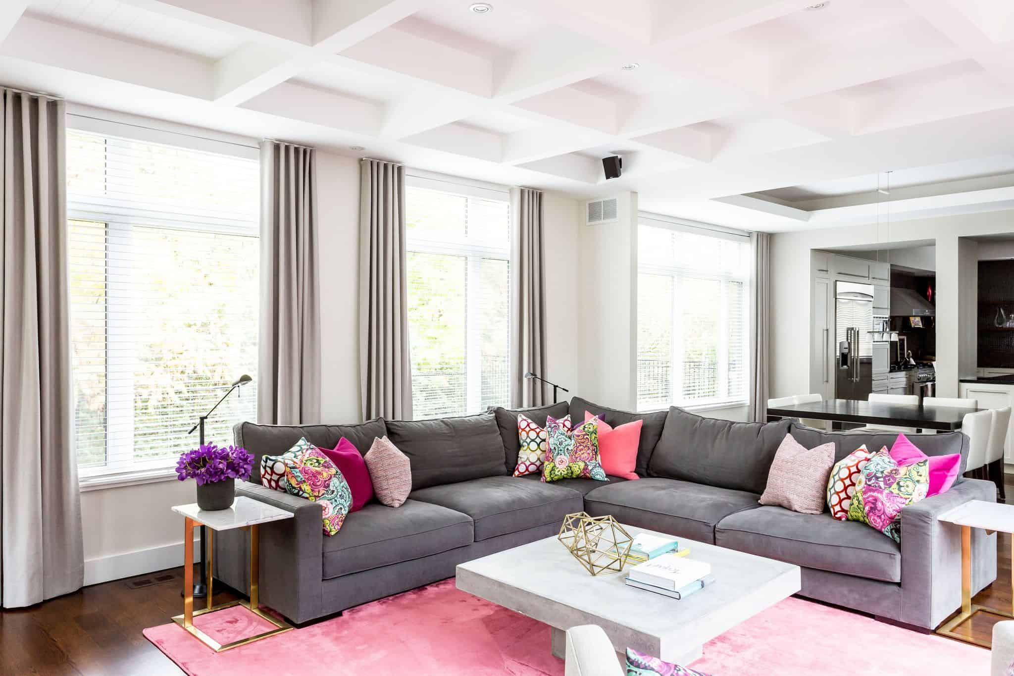 Gray corner couch inside a living room with a pink carpet